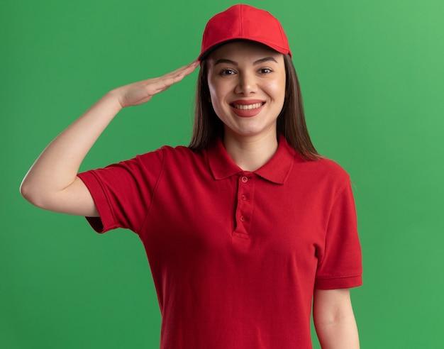 Glimlachende mooie bezorger in uniform die een groetgebaar doet