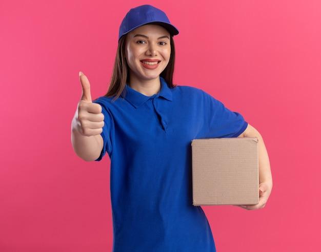 Glimlachende mooie bezorger in uniform duimen omhoog en houdt cardbox vast