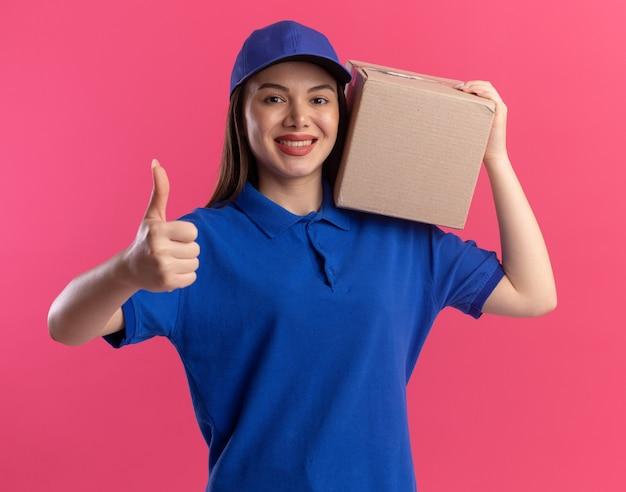 Glimlachende mooie bezorger in uniform duimen omhoog en houdt kartonnen doos op schouder