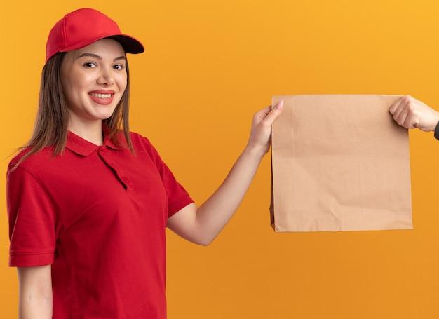 Glimlachende mooie bezorger in uniform geeft papieren pakket aan iemand die naar de camera kijkt