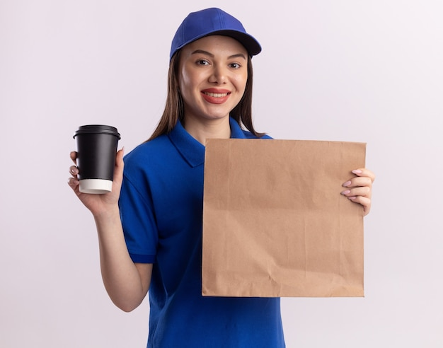 Glimlachende mooie bezorger in uniform houdt papieren pakket en papieren beker vast