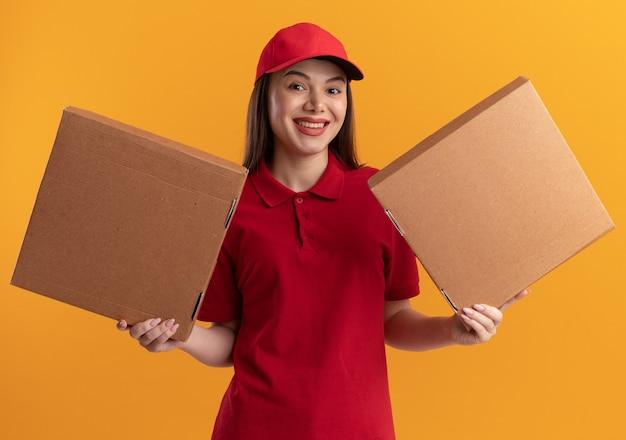 Glimlachende mooie bezorger in uniform houdt pizzadozen op twee handen vast