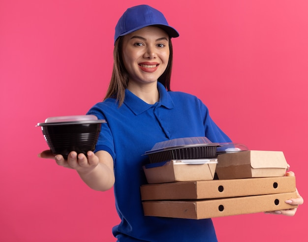 Glimlachende mooie bezorger in uniform houdt voedselcontainer en voedselpakketten op pizzadozen