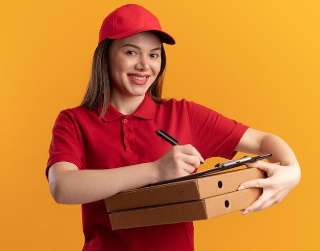 Glimlachende mooie bezorger in uniform schrijft op klembord met marker die pizzadozen vasthoudt geïsoleerd op oranje muur met kopieerruimte