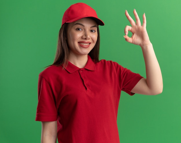Glimlachende mooie bezorger in uniforme gebaren ok handteken geïsoleerd op groene muur met kopieerruimte