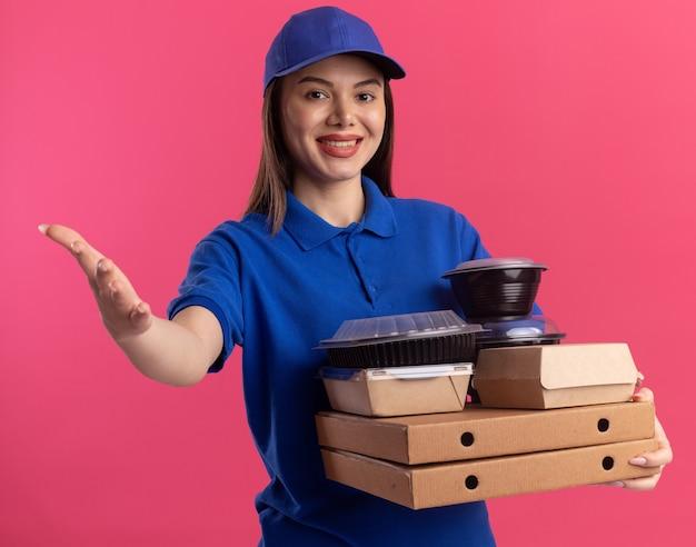 Glimlachende mooie bezorger in uniforme punten met hand en houdt voedselpakket en containers op pizzadozen geïsoleerd op roze muur met kopie ruimte