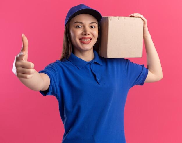 Glimlachende mooie bezorgvrouw in uniform beduimelt omhoog en houdt kartonnen doos op de schouder op roze