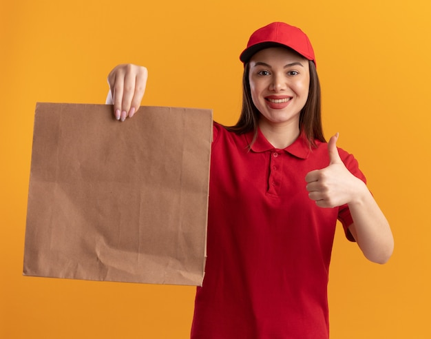 Glimlachende mooie bezorgvrouw in uniform beduimelt omhoog en houdt papieren pakket op oranje
