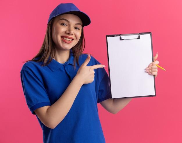 Glimlachende mooie bezorgvrouw in uniforme ruimen en punten op klembord geïsoleerd op roze muur met kopie ruimte