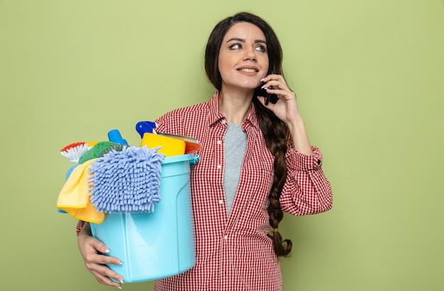 Glimlachende mooie blanke schonere vrouw die schoonmaakapparatuur vasthoudt en aan de telefoon praat terwijl ze naar de zijkant kijkt