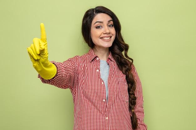 Glimlachende mooie blanke schonere vrouw met rubberen handschoenen die omhoog wijst en kijkt