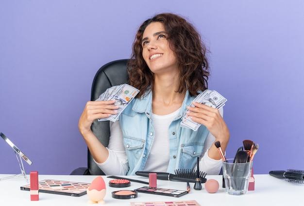 Glimlachende mooie blanke vrouw die aan tafel zit met make-uptools die geld vasthoudt en omhoog kijkt