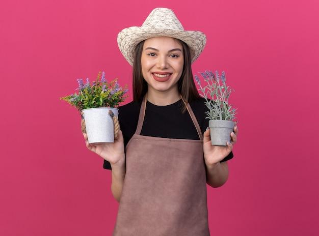 Glimlachende mooie blanke vrouwelijke tuinman die een tuinhoed draagt en bloempotten vasthoudt
