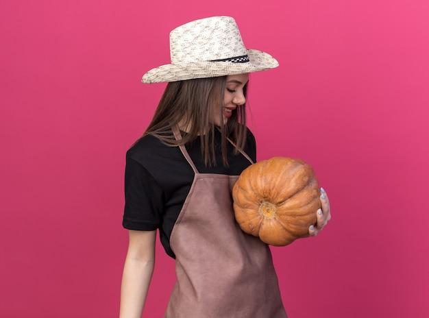 Glimlachende mooie blanke vrouwelijke tuinman met een tuinhoed die pompoen vasthoudt en kijkt naar een roze muur met kopieerruimte