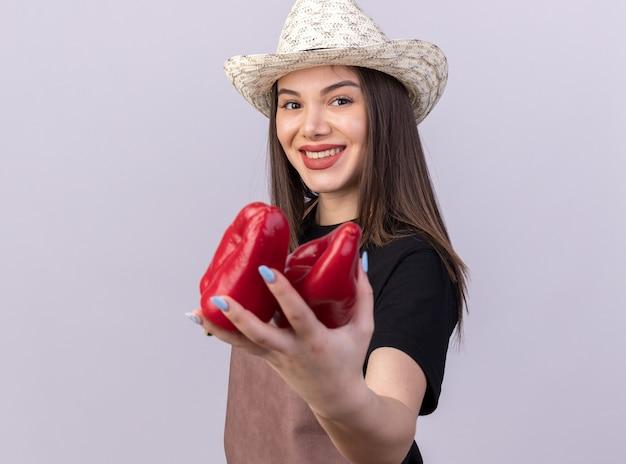 Glimlachende mooie blanke vrouwelijke tuinman met een tuinhoed met rode paprika's geïsoleerd op een witte muur met kopieerruimte
