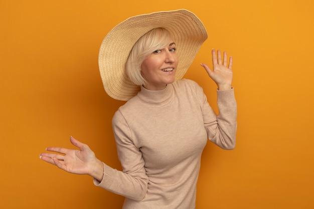 Glimlachende mooie blonde slavische vrouw met strandhoed staat met opgeheven handen op sinaasappel
