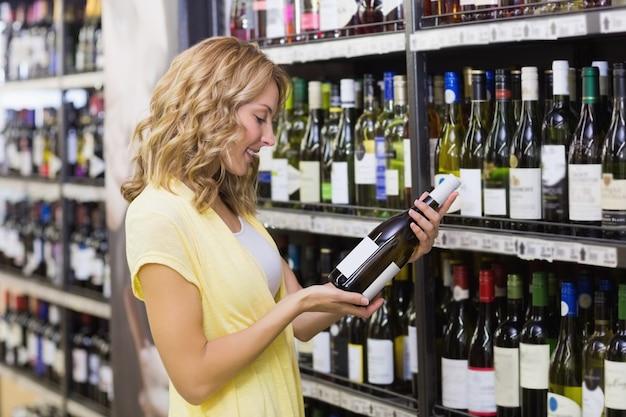 Glimlachende mooie blondevrouw die wijnfles bekijken
