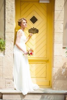 Glimlachende mooie bruid op huwelijksdag met een groot boeket dichtbij kerk.