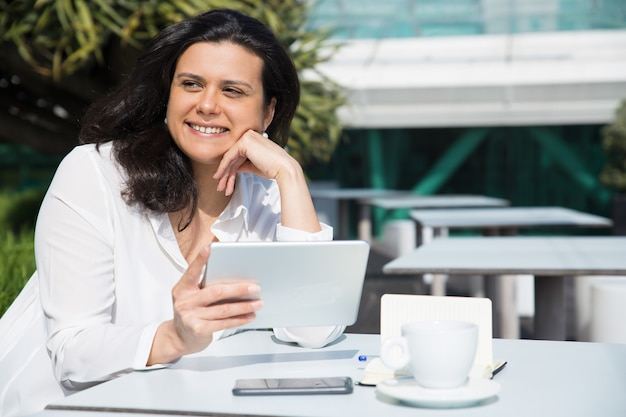 Glimlachende mooie dame die en tablet in straatkoffie werken gebruiken