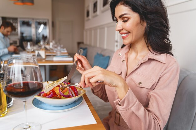 Glimlachende mooie dame die verse salade eet terwijl ze aan tafel zit met eten en wijn