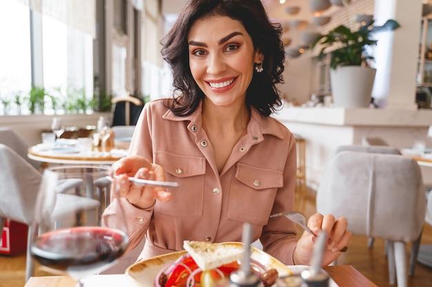 Glimlachende mooie dame die vork en mes vasthoudt terwijl ze aan tafel zit met heerlijk gezond eten en wijn