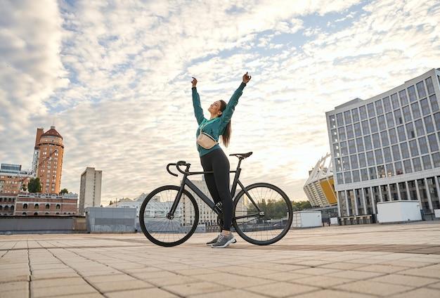 Glimlachende mooie dame in sportkleding die in de buurt van de fiets staat en 's ochtends tegen de bewolkte hemel poseert. sport en lifestyle concept