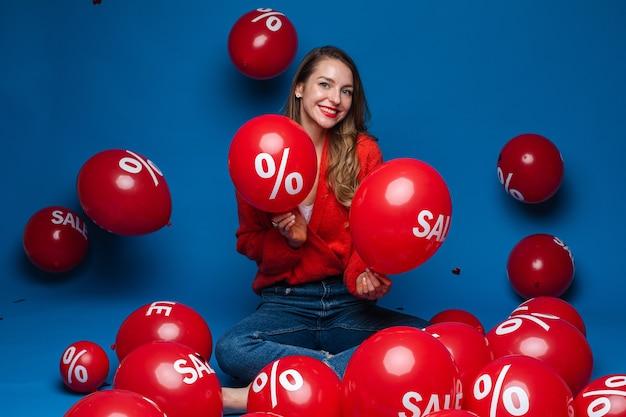 Glimlachende mooie dame met twee rode ballonnen, geïsoleerd op blauwe muur