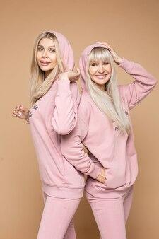 Glimlachende mooie dames die comfortabele roze sportpakken dragen terwijl ze naast elkaar staan terwijl ze naar de camera kijken, geïsoleerd op een bruine achtergrond