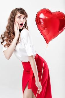 Glimlachende mooie gekrulde vrouw met hartvormige luchtballons voor st. valentijnsdag