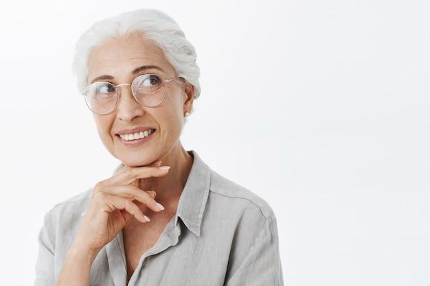 Glimlachende mooie hogere vrouw die in glazen dromerige rechterbovenhoek kijkt