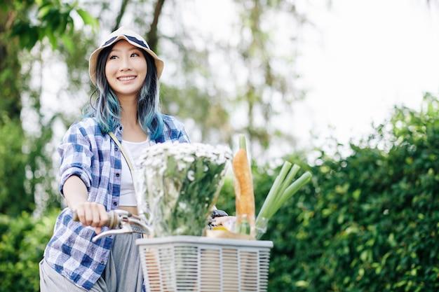 Glimlachende mooie jonge chinese vrouw die op fiets met bloemboeket en voedsel voor mand berijdt