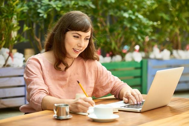 Glimlachende mooie jonge freelancer die op een terras werkt, e-mails controleert op de laptop en aantekeningen maakt in de planner