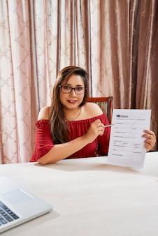 Glimlachende mooie jonge manager die een formulier toont dat de klant moet invullen om een lening te krijgen
