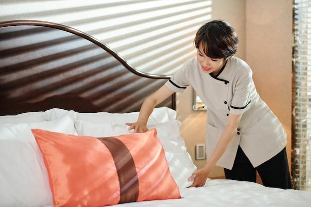Glimlachende mooie jonge meid die kussens op bed in hotelkamer aanpast
