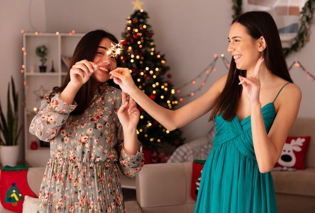 Glimlachende mooie jonge meisjes die hun wonderkaarsen kruisen die thuis van kerstmis genieten