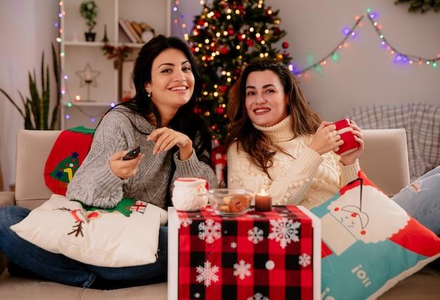 Glimlachende mooie jonge meisjes houden tv op afstand zittend op fauteuils en genietend van de kersttijd thuis