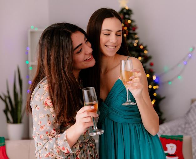Glimlachende mooie jonge meisjes met glazen champagne die thuis genieten van kersttijd