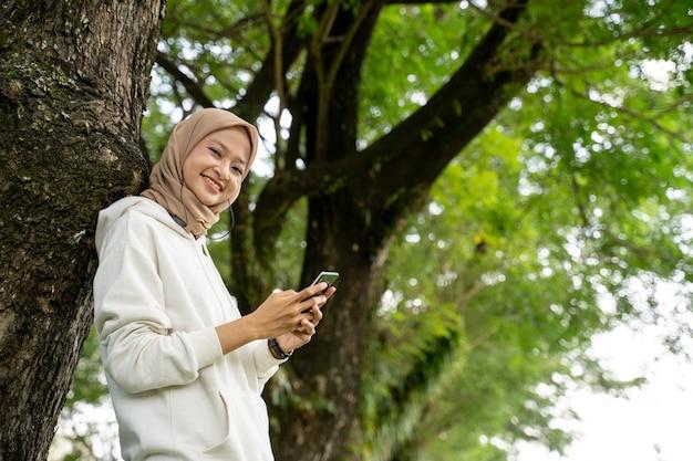 Glimlachende mooie jonge moslimvrouw die mobiele telefoon met behulp van tijdens oefeningspauze openlucht
