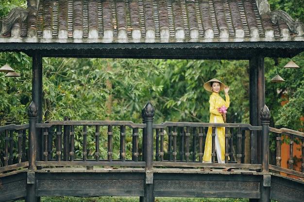 Glimlachende mooie jonge vietnamese vrouw in gele jurk en hoed staande op brug met stelletje lo...
