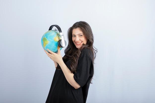 Glimlachende mooie jonge vrouw die en een bol in hoofdtelefoons bevindt zich houdt.