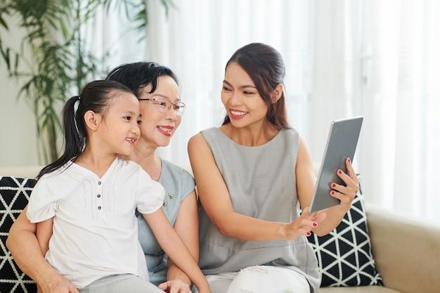 Glimlachende mooie jonge vrouw die foto's op tabletcomputer toont aan haar hogere moeder en kleine dochter
