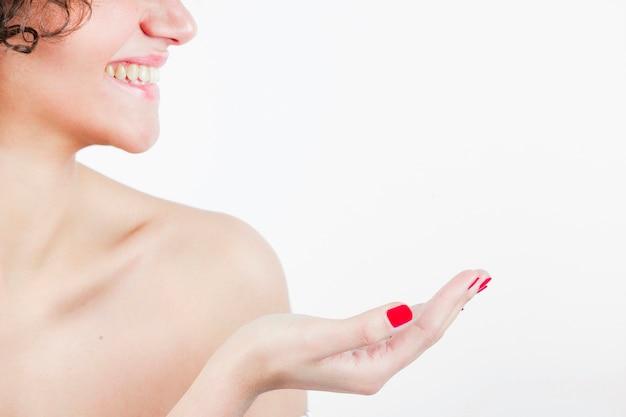 Glimlachende mooie jonge vrouw die haar hand toont tegen witte achtergrond