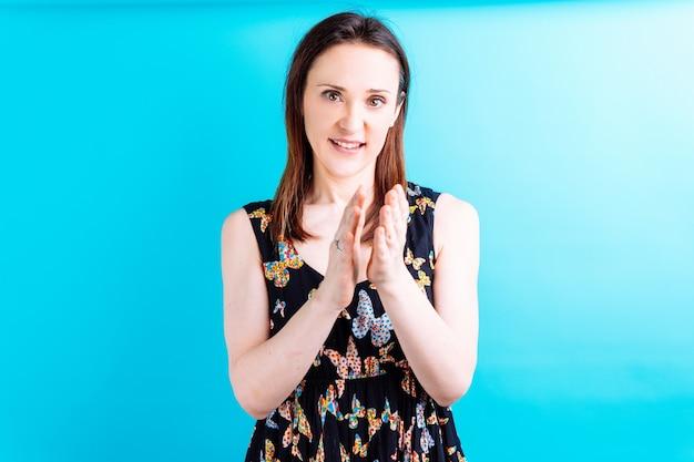 Glimlachende mooie jonge vrouw die haar handen op blauwe achtergrond klapt. feliciteer concept