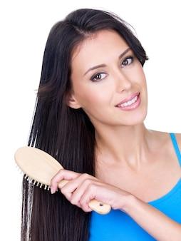 Glimlachende mooie jonge vrouw die haar lang bruin haar kamt met geïsoleerde haarborstel -
