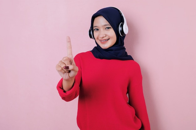 Glimlachende mooie jonge vrouw die iets richt dat rode t-shirt draagt die hoofdtelefoon gebruikt