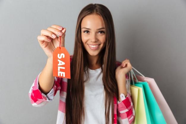 Glimlachende mooie jonge vrouw die verkoopteken toont en het winkelen zakken houdt
