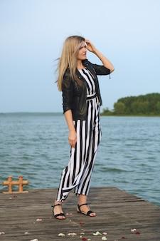 Glimlachende mooie jonge vrouw die zich op pijler in winderig weer bevindt