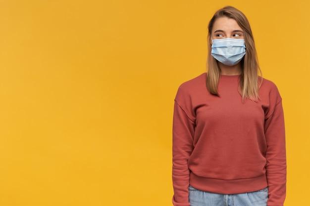 Glimlachende mooie jonge vrouw in terracottasweatshirt die het koude gezichtsmasker van de beschermingsgriep dragen en aan de kant over gele muur kijken