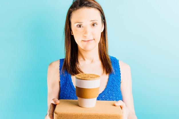 Glimlachende mooie jonge vrouw met blauwe achtergrond die een herbruikbare koffiekop op een yogabaksteen houdt