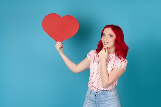 Glimlachende mooie jonge vrouw met rood haar die rood document hart houdt en haar kin krabt